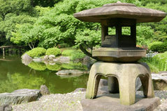 Japanese outdoor stone lantern and lake in zen garden Royalty Free Stock Image