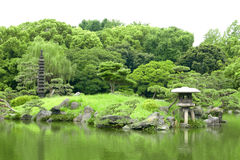 Japanese outdoor stone lantern and lake in zen garden Royalty Free Stock Photography