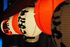 Japanese paper lanterns at night. Six red and white paper Japanese lanterns lit up at night Royalty Free Stock Images
