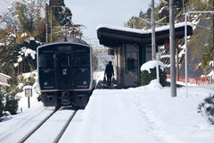 Japanese passenger train at station on a snowy day Stock Images