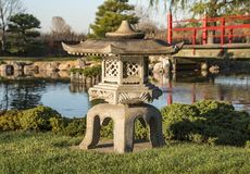 Japanese pedestal lantern near a pond. Bloomington, MN/USA - October 22, 2016: A Japanese pedestal lantern at the Japanese Garden at Normandale Community College Stock Image