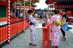 Japanese people hold and shaking Fortune Sticks at Fushimi Inari. Japanese people wear traditional Japanese clothing (Kimono and Yukatas) hold and shaking stock image