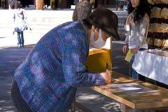 Japanese people pray shrine ema. Japanese woman with mask praying at Meiji Jingu shrine Royalty Free Stock Image