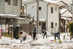 Japanese people removing snow with a shovel Stock Photography