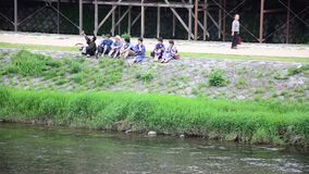 Japanese people sit and talk at riverside of Kamo River in Kyoto, Japan stock video footage