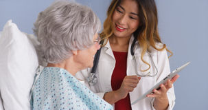Japanese physician using tablet talking with mature woman patient Royalty Free Stock Photography
