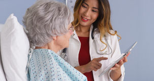 Japanese physician using tablet talking with mature woman patient Royalty Free Stock Images
