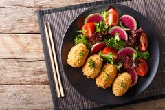 Japanese potato korokke and fresh vegetables close-up. horizonta. Japanese potato korokke and fresh vegetables close-up on a plate. Horizontal top view from Royalty Free Stock Images