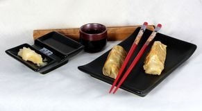 Japanese potstickers with ginger, soy and sake. Red chopsticks angle across a black matte plate with two potstickers, lightly browned. The side dish is divided royalty free stock images