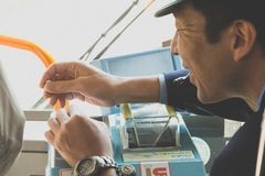 Japanese public bus driver gives the change to a passenger Stock Photo