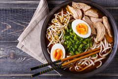 Japanese ramen soup with chicken, egg, chives and sprout. Japanese ramen soup with chicken, egg, chives and sprout on dark wooden background stock image