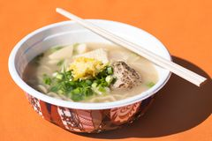 Japanese ramen soup. Japanese taste ramen soup with noodles,green onion,meat, served in bowl and wooden sticks on the table with orange tablecloth stock photo