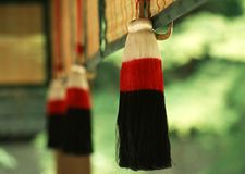 A Japanese red and black hanging traditional decorative item with green background blurred stock photography