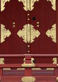 A Japanese red door with gold details and railings in front background stock images