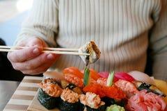 Japanese restaurant. The man at the Japanese restaurant eats sushi Royalty Free Stock Images