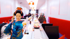 Japanese restaurant. Interior design with geisha doll on foreground Royalty Free Stock Images