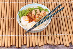 Japanese rice topped boil eggs and fried pork. Royalty Free Stock Image