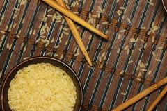 Japanese rice in a wooden bowl. Wooden chopsticks On the table of a bamboo mat. Asian cuisine. View from above. stock photo
