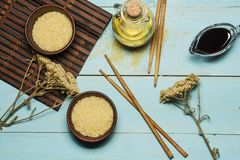 Japanese rice in a wooden bowl. Wooden chopsticks On the table of a bamboo mat. Asian cuisine. View from above. royalty free stock images