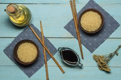 Japanese rice in a wooden bowl. Wooden chopsticks On the table of a bamboo mat. Asian cuisine. View from above. royalty free stock photo