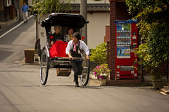 Japanese rickshaw. KYOTO, JAPAN - MAY 9: Two women in a rickshaw pulled by a young tour guide on a street in Kyoto, Japan Stock Photos