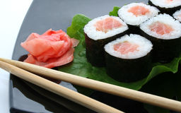 A Japanese roll. A sushi roll with ginger and stick on Japanese plate Royalty Free Stock Image