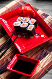 Japanese roll with salmon on red plate Royalty Free Stock Photo