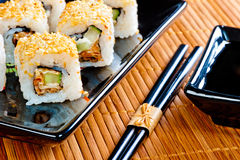 Japanese rolls on beautiful black crockery Stock Photography