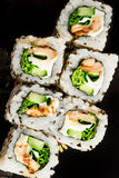 Japanese rolls on a black dish Royalty Free Stock Images