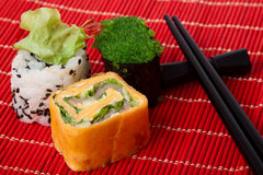 Japanese rolls with chopstick. On a red bamboo napkin Stock Photo