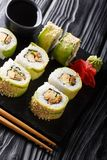 Japanese rolls green dragon with avocado, omelette tamago, sesame and cucumber closeup on a plate. vertical stock images