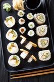 Japanese rolls Hosomaki, Uramaki, Maki, Nigiri, Tamagoyaki with various fillings close-up on a plate. Vertical top view. Japanese rolls Hosomaki, Uramaki, Maki stock photos