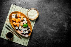 Japanese rolls on a plate with rice and soy sauce. On a black rustic background stock photography