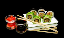 Japanese rolls, soy sauce and pickled ginger on a black backgrou Royalty Free Stock Photo