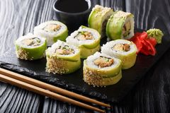 Japanese rolls wrapped in avocado with omelet, sesame and cucumber closeup on a plate. horizontal stock image
