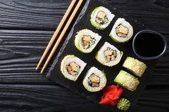 Japanese rolls wrapped in avocado with omelet, sesame and cucumber closeup on a plate. horizontal top view stock photos