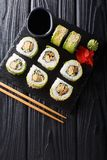 Japanese rolls wrapped in avocado with omelet, sesame and cucumber closeup on a plate. Vertical top view royalty free stock photography