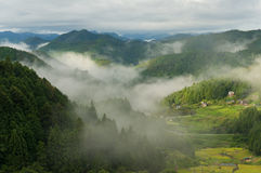 Japanese rural landscape of mountain farms on foggy morning Royalty Free Stock Images
