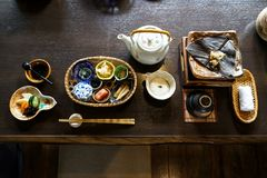 Japanese ryokan breakfast appetizer dishes including mentaiko, pickle, seaweed, bamboo shoot, hot plate, other side dishes. Green tea pot, cup and warm towel royalty free stock photo