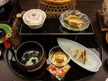 Japanese ryokan kaiseki dinner appetizer including cherry blossom tofu, lily bulb tofu, horse tail, silvervine and sesame royalty free stock images