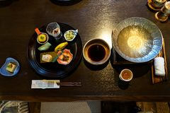 Japanese ryokan kaiseki dinner appetizer including hors d`oeuvres dishes, hot pot preparation, soy sauce bowl, liquor cup stock images