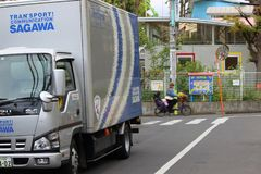 Moving company truck and a bicycle. Japanese Sagawa moving company truck standing on the road and a bicycle on the street in Tokyo, Japan royalty free stock images