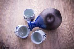 Japanese Sake drinking set. On old wood texture background Royalty Free Stock Images