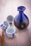Japanese Sake drinking set. On old wood texture background Stock Images