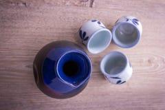 Japanese Sake drinking set. On old wood texture background (focus on sake jug Stock Image
