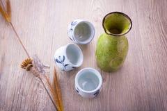 Japanese Sake drinking set. On old wood texture background (focus on sake jug Royalty Free Stock Images