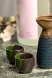 Japanese sake setup with flowers in background Stock Photo