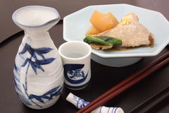 Japanese Sake with simmered Japanese amberjack and white radish Royalty Free Stock Photos