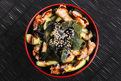 Japanese salad with seaweed and soy sauce chicken and avocado. Sesame and cucumber on a black table Stock Photo