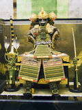 Japanese samurai armor. An ancient japanese samurai armor with gold details and silk finishing, with a sword a two arrows Royalty Free Stock Photography